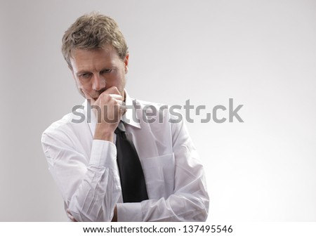 Portrait of a mature businessman looking down worried - stock photo