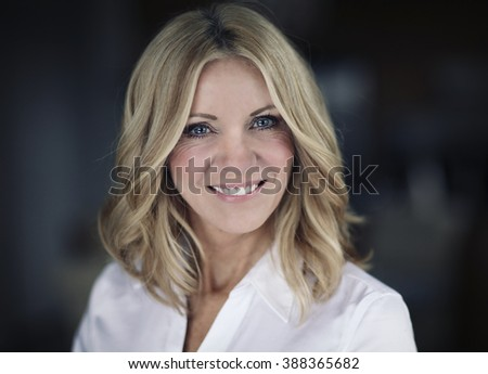 Portrait Of A Mature Businesswoman Smiling Looking away - stock photo