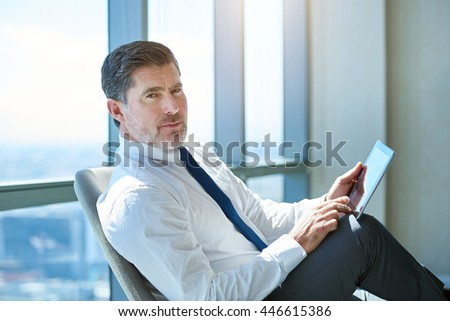 Portrait of a mature CEO sitting in his office, comfortably using a digital tablet, and looking at the camera with a serious yet positive expression - stock photo