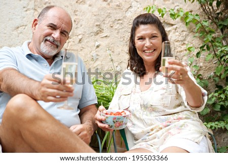Portrait of a mature couple a luxury home garden on holiday toasting with champagne and eating strawberries, relaxing together on vacation. Senior people enjoying retirement, outdoors lifestyle. - stock photo