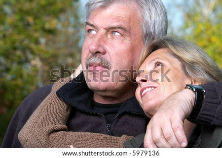 Portrait of a mature couple embracing each other and looking sidewards. - stock photo