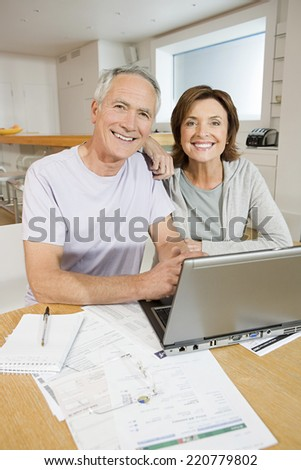 Portrait of a mature couple sitting at a kitchen table working on household bills - stock photo
