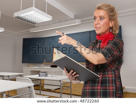 Portrait of a mature female teacher in a classroom pointing to someone