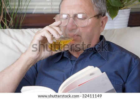 Portrait of a mature gentleman drinking beer while reading a book - stock photo