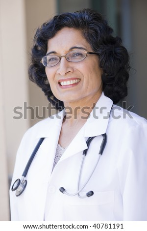 Portrait of a Mature Indian Female Doctor Standing Outdoors - stock photo