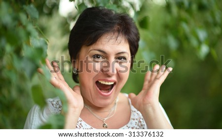 Portrait of a mature lady surprised at summer outdoors