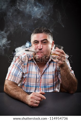 Portrait of a mature mafia man drinking and smoking while sitting at table on gray background