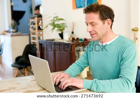 Portrait of a mature male adult sitting at table at home using laptop  - stock photo