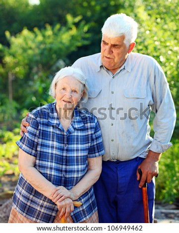 Portrait of a mature man and his senior mother outdoors - stock photo