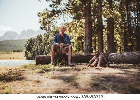 Portrait of a mature man sitting on a log staring out to the lake. Senior man camping by the lake on a summer day. - stock photo