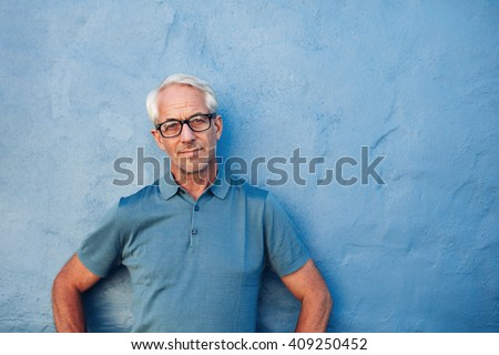 Portrait of a mature man standing against a blue background with copy space. Caucasian man wearing glasses leaning to a wall and staring at camera. - stock photo