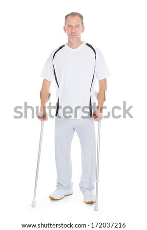 Portrait Of A Mature Man With Crutches Isolated Over White Background