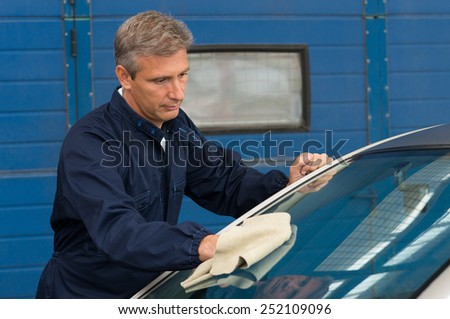 Portrait Of A Mature Mechanic Cleaning Windshield With A Cloth At Garage - stock photo