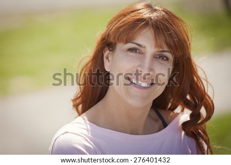 Portrait Of A Mature Red woman smiling at the camera - stock photo
