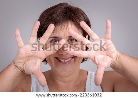 Portrait of a mature woman against a grey background. - stock photo