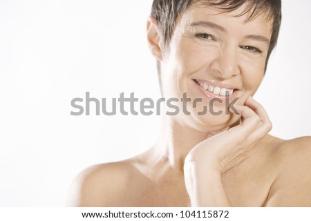 Portrait of a mature woman against a white background, smiling. - stock photo