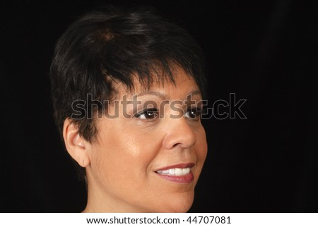 portrait of a mature woman against black background - stock photo
