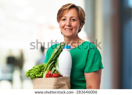 portrait of a mature woman carrying a shopping bag with food - stock photo