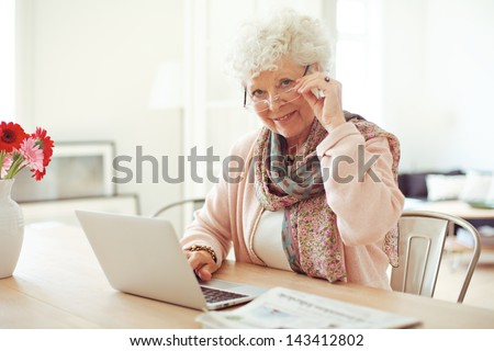 Portrait of a mature woman with laptop smiling at you - stock photo