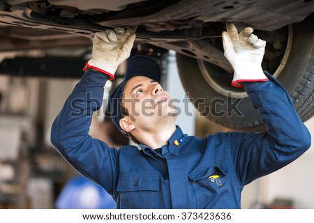 Portrait of a mechanic checking the condition a lifted car - stock photo