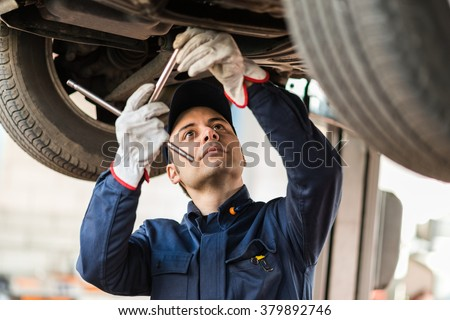 Portrait of a mechanic repairing a lifted car - stock photo