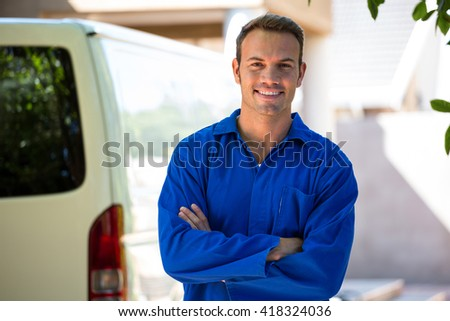 Portrait of a mechanic standing near his car - stock photo