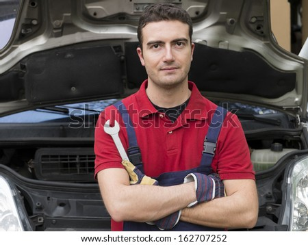 portrait of a mechanic with arms folded in auto repair shop - stock photo