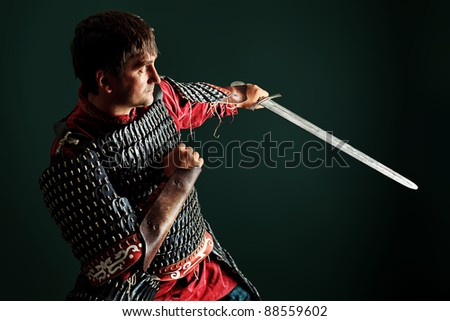 Portrait of a medieval male knight in armor over black background. - stock photo