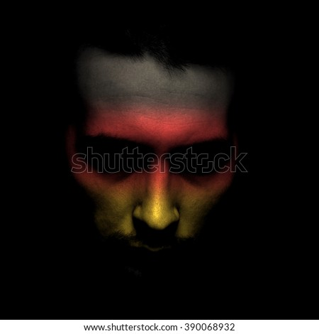 Portrait of a men with the flag of the German painted on face. - stock photo
