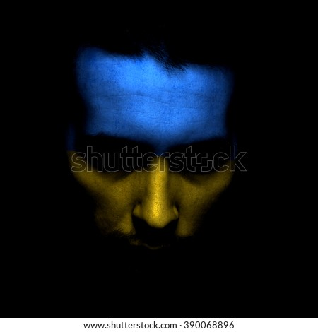 Portrait of a men with the flag of the Ukrainian painted on face. - stock photo