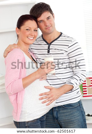 Portrait of a merry pregnant woman holding a glass of milk and of her husband touching her belly at home - stock photo