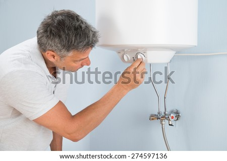 Portrait Of A Mid-adult Man Adjusting Temperature Of Electric Boiler - stock photo