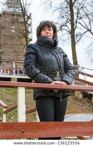 portrait of a middle-aged brunette woman in a black jacket outdoors