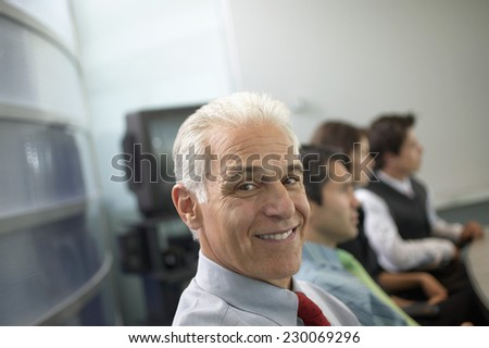 Portrait of a middle aged businessman posing for the camera during a meeting - stock photo