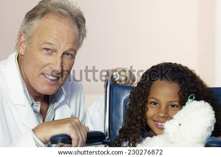 Portrait of a middle aged doctor posing with a young girl in a wheelchair - stock photo