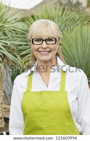 Portrait of a middle-aged florist in greenhouse - stock photo