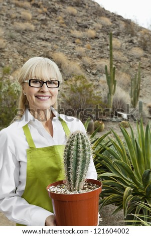 Portrait of a middle-aged gardener holding potted cactus plant - stock photo
