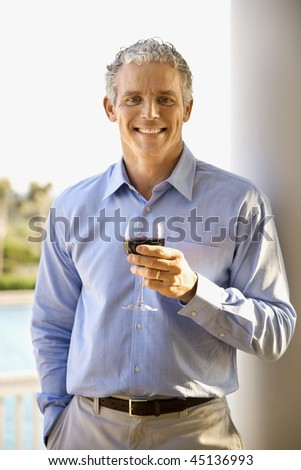 Portrait of a middle aged man on a terrace drinking red wine. Vertical shot.