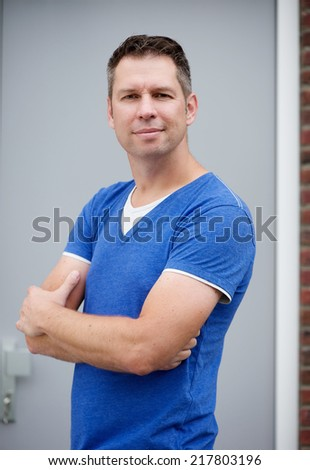 Portrait of a middle aged man smiling with arms crossed - stock photo