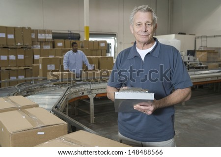 Portrait of a middle aged man with worker in background at distribution warehouse - stock photo