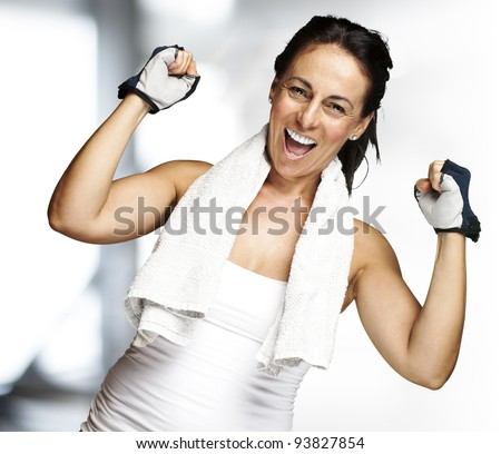portrait of a middle aged woman gesturing a win symbol indoor