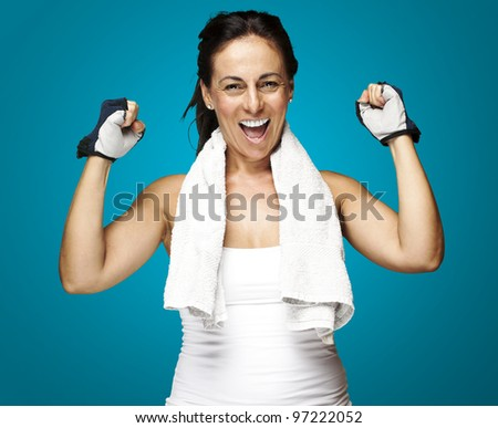 portrait of a middle aged woman gesturing a win symbol over a blue background