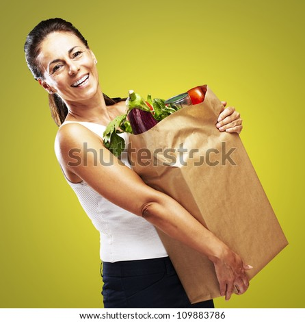 portrait of a middle aged woman holding the purchase over a yellow background - stock photo