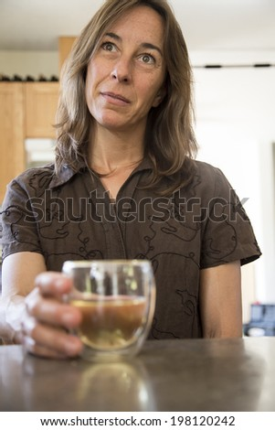 Portrait of a middle aged woman in the kitchen drinking wine. - stock photo