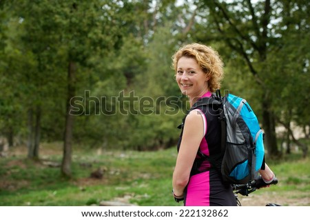 Portrait of a middle aged woman smiling with bicycle - stock photo