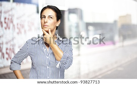 portrait of a middle aged woman thinking against a street background