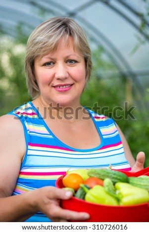 Portrait of a middle-aged woman with vegetables in a bowl - stock photo