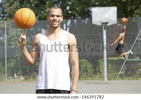 Portrait of a mixed race Basketball Player Spinning the ball and smiling to camera - stock photo