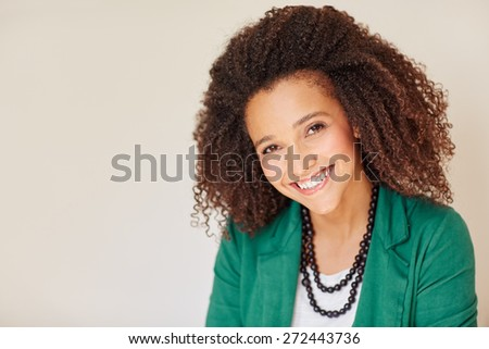 Portrait of a mixed race businesswoman smiling at the camera with a beautiful curly afro hairstyle  - stock photo