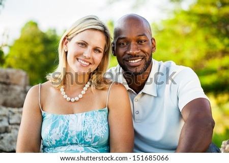 Portrait of a mixed race couple sitting at the park in summer - stock photo